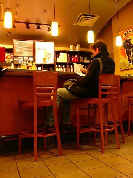 カフェにて読み物をする男性