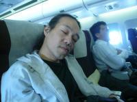 5/16 帰りの機内。眠る村山義光氏。お疲れ様でした